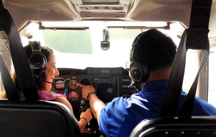 A flight student smiling as the instructor points to a gauge on a dashboard