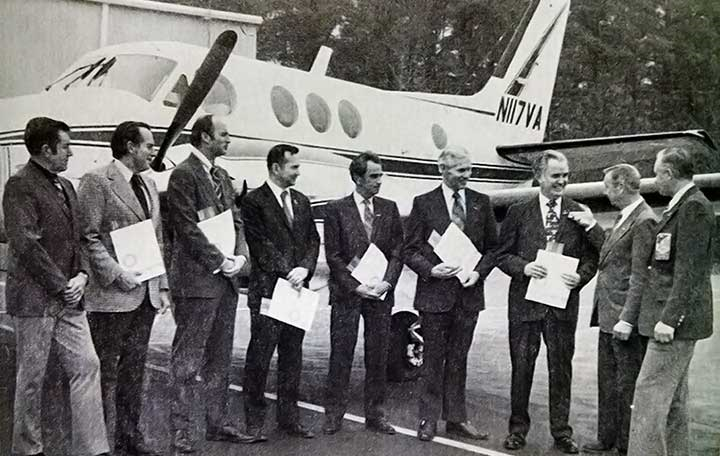 An old photo of men in front of an airplane